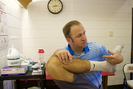 Scott Hooker, head athletic trainer, stretches out soccer player Michael Sass, a senior exercise science major.
