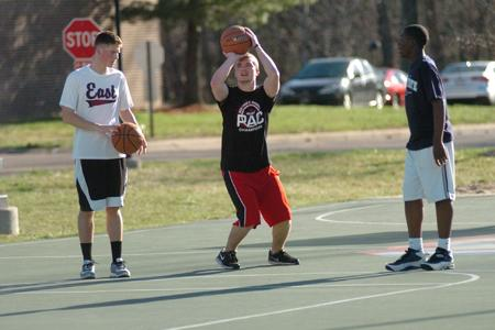 Sophomore engineering major Ian Mathis and sophomore elementary education major Nicholas Herron play basketball outside of the C-store with a friend's brother, Corey Kirkland, 13. Both students live in the Marshall apartment complex on campus.