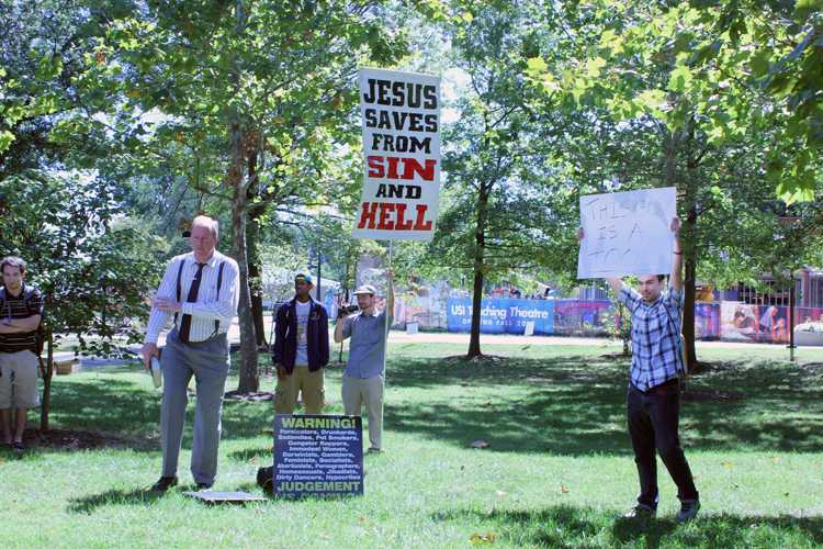 Street evangelist James Gilles (left) preaches to a crowd on campus Monday, which prompted USI student Spencer Kiessling (right) to create the sign he's holding.